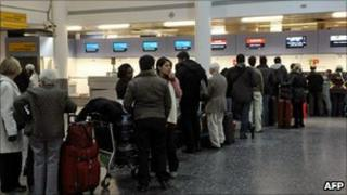 Gatwick Airport passengers wait at the check-in desk