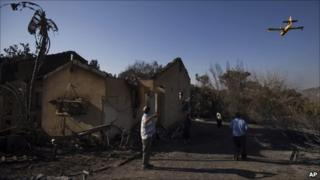 As a firefighting plane flies over, members of the Cohen family walk next to the remains of their house, burnt in the fire, in the youth village (boarding school) of Yemin Orde, near the northern city of Haifa, Israel, Sunday, Dec. 5, 2010
