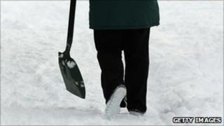 Man carrying shovel through snow