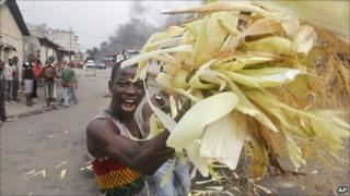 A supporter of Alassane Ouattara throws maize onto a fire in Abidjan