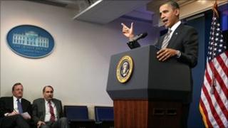 Robert Gibbs, right, and David Axelrod, centre listen to President Barack Obama talk about a tax cut deal