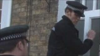 Police officers knock on the door of a house during the operation