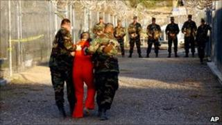 A prisoner walking with US soldiers at Guantanamo Bay prison