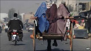 Afghan women travel on horse-drawn cart in Kandahar city, south of Kabul, Afghanistan, Tuesday, Nov 23, 2010.