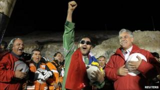 The last miner to be rescued, Luis Urzua, who is credited with organizing the miners to ration food and save themselves, gestures next to Chilean President Sebastian Pinera on 13 October