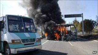 A bus burns and another sits with burst tyres on a road leading into Morelia, Mexico