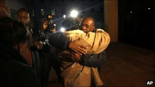 Relatives of Henry Glover embracing