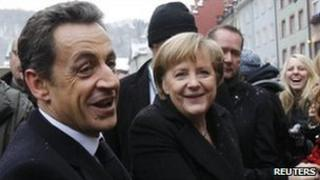 French President Nicolas Sarkozy (left) and German Chancellor Angela Merkel meet members of the public in Freiburg, 10 December