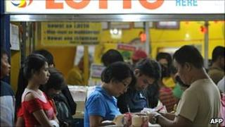 People fill out their lottery cards at a lottery outlet in Manila on 29 November 2010