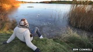 A student looks over the thawing ice at Sandy Water Park, Llanelli