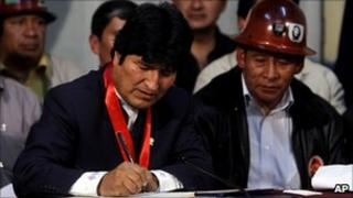 Evo Morales (left) signing the pensions law beside a trade union leader