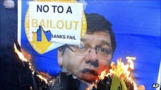 Anti-bail-out protesters burn a placard with the face of Taoiseach Brian Cowen on it