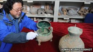 A Shaanxi Provincial Archeological Institute official displays the bronze vessel thought to contain the ancient soup