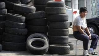 A dealer sits next to tyres on display at a tyre shop in Beijing