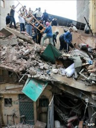 Rescue workers search a collapsed building in Alexandria, Egypt, 12 December 2010
