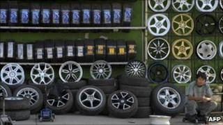 A man sits next to tyres on display at a tyre shop in Beijing