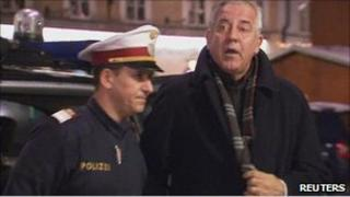 Croatian former Prime Minister Ivo Sanader is escorted by an Austrian policeman in Salzburg after being arrested, 10 December