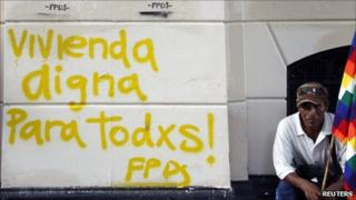 man holds a Wiphala indigenous flag next to graffiti calling for decent housing for all during a demonstration to demand housing for homeless people outside Buenos Aires City Hall on 14 December, 2010
