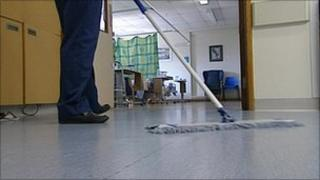 A hospital cleaner mopping a floor