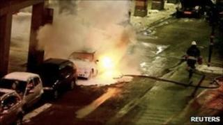 Video footage showing a firefighter attempting to put out the fire on a burning car in Stockholm (11 December 2010)