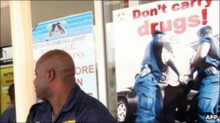 A security official at Ghana's Kotoka International Airport in 2007 in front of drug prevention posters