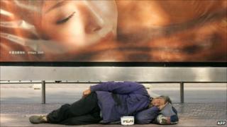 File image of a homeless man sleeping underneath an advertising board in Beijing