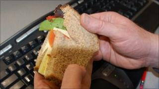Man holding sandwich over computer keyboard