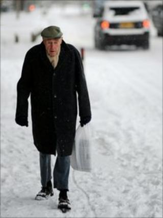 Elderly man walking in snow