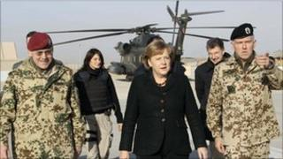 German Chancellor Angela Merkel (centre) arrives for a visit at an army camp in Kunduz, northern Afghanistan, on Saturday