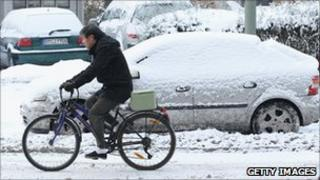 A man rides a bicycle past parked cars covered in ice and snow in Berlin, Germany, 19 December 2010