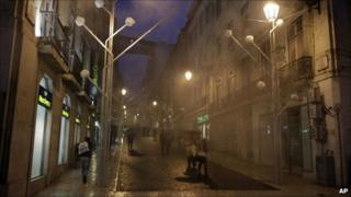 People walk under rain in central Lisbon, Portugal