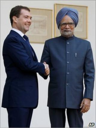 Russian President Dmitry Medvedev, left, poses for photographs with Indian Prime Minister Manmohan Singh in New Delhi, India, Dec. 21, 2010.