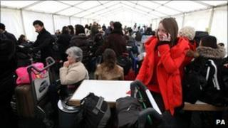 Passengers wait in a marquee outside Terminal 3