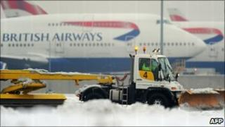 A worker operates a snow plough near the second runway at Heathrow