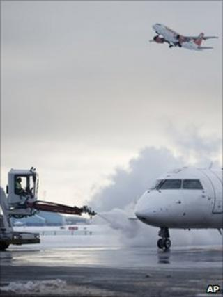An aircraft takes off as another is de-iced at Copenhagen's Kastrup International Airport, 21 December 2010