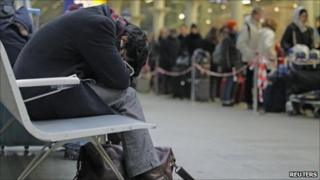 A passenger attempts sleep as Eurostar passengers queue for trains at St Pancras station in London