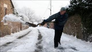 A man clears snow and ice from the road