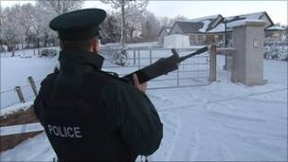 A police officer guards the house which was targeted in the grenade attack