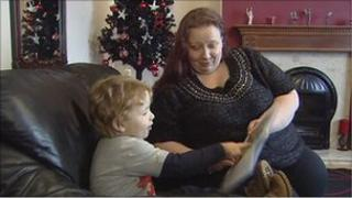 Mother and son reading story book in front of Christmas tree
