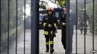 Italian firefighters and a policeman leave the Swiss embassy in Rome, 23 December