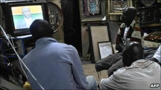 People watch television in Abidjan