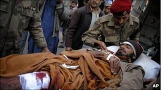 Pakistani soldiers help an injured man as he arrives at hospital in Peshawar