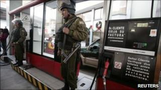 Police stand guard at a petrol station in La Paz, 26 Dec