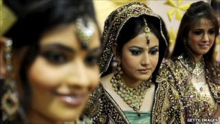 Indian models display bridal wear during a bridal make-up workshop in Amritsar, August 2010