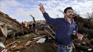 A man standing near debris from a tornado in Arkansas