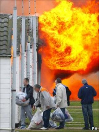Prisoners carry bags into a jail building as flames engulf part of the compound