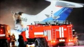 A grab taken on January 1, 2011 from the Russian NTV channel shows firefighters standing in front of the wreckage of the Russian passenger Tu-154 aircraft after it burst into flames