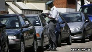 A traffic warden inspecting parked cars