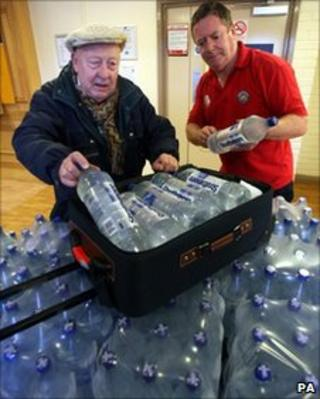 Elderly man packing water bottles into suitcase