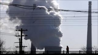 A chimney billows smoke from a coal-burning power station behind powerlines and railway tracks in Beijing